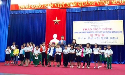 Lãnh đạo TP.Tam Kỳ và Công ty Panko Tam Thăng trao học bổng cho học sinh. Ảnh: X.P