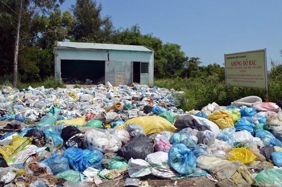 Người dân vứt rác vô tội vạ ngay dưới biển cấm. Ảnh: K.LINH