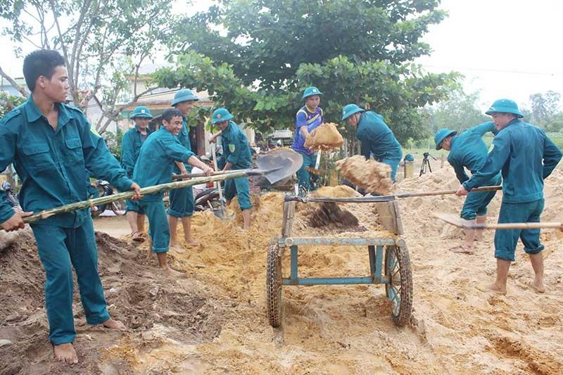 Lực lượng dân quân giúp dân làm đường giao thông nông thôn. Ảnh: T.A