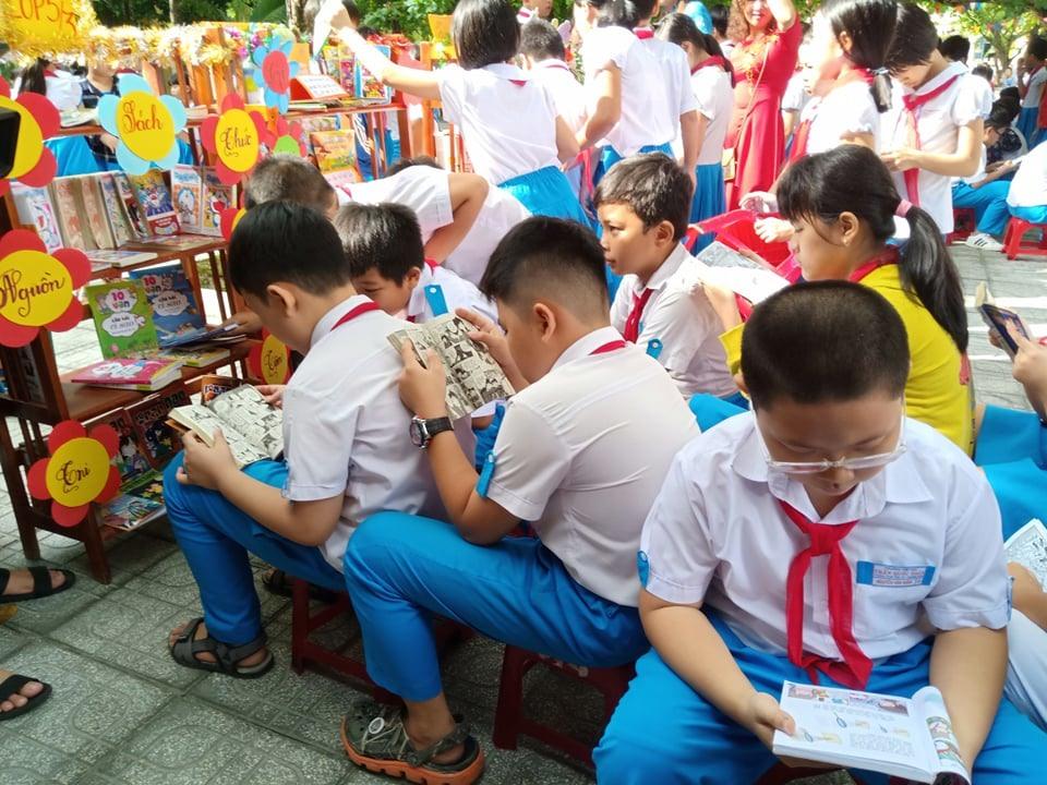 Học sinh đọc sách ở sân trường trong ngày khánh thành thư viện thân thiện. Ảnh: C.N