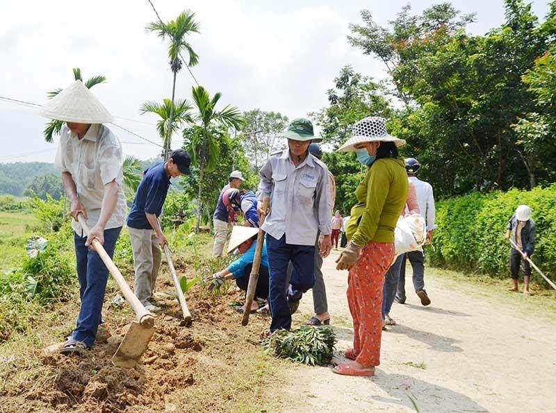 Hội viên Cựu chiến binh và người dân thôn Hội An (xã Tiên Châu) dọn vệ sinh môi trường, trồng hoa dọc tuyến đường bê tông nông thôn. Ảnh: N.H
