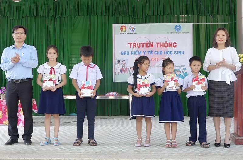 Trao thẻ BHYT miễn phí cho học sinh nghèo tại Trường TH Trần Quốc Toản.Ảnh: BIÊN THỰC