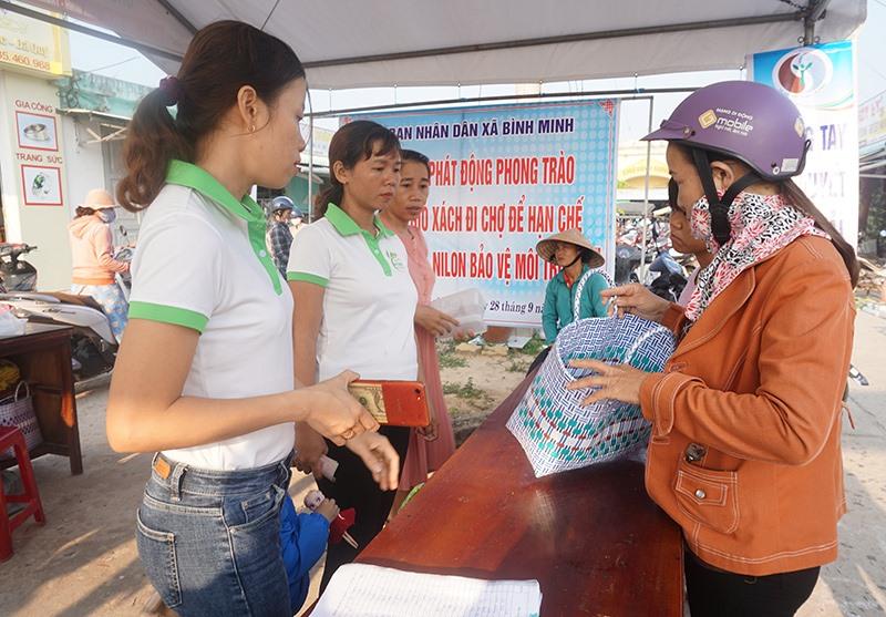 Người dân Bình Minh đã bắt đầu làm quen với việc dùng giỏ xách khi đi chợ. Ảnh: G.BIÊN
