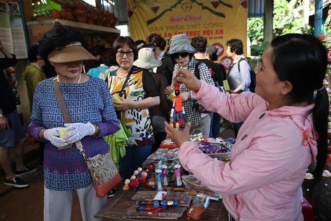 Tourists at a souvenir shop in Thanh Ha village. Photo: CAND