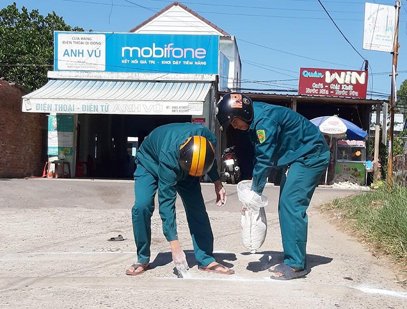 Rải vôi bột trên những trục đường chính của huyện Duy Xuyên để hạn chế nguy cơ dịch bệnh lây lan. Ảnh: N.P