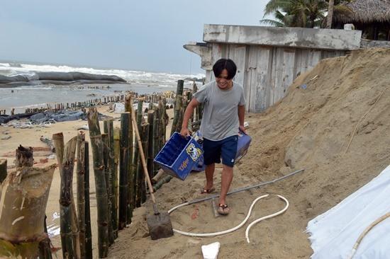 ... và lấy thùng bia đổ cát chồng lên trên để ngăn sóng đánh vào bờ.