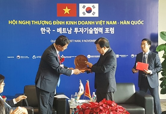 Mr. Dung gives Mr. Joo Hyung Chul PM Nguyen Xuan Phuc's gift (symbol of the two world heritages in Quang Nam: Japanese bridge in Hoi An ancient town and My Son Sanctuary)