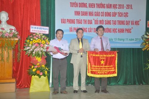 Phó Chủ tịch UBND tỉnh Trần Văn Tân tặng Cờ thi đua xuất sắc của UBND tỉnh cho Phòng GD-ĐT Duy Xuyên và Trường Phổ thông Dân tộc nội trú tỉnh. Ảnh: X.P