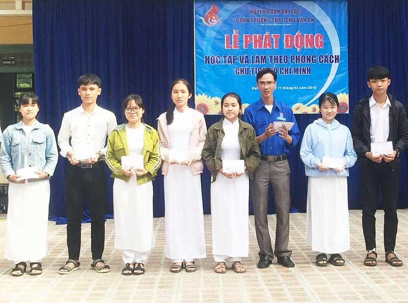 Thầy giáo Trần Minh Giang (áo xanh ở giữa) tặng quà cho các em học sinh - Ảnh: THÁI CƯỜNG