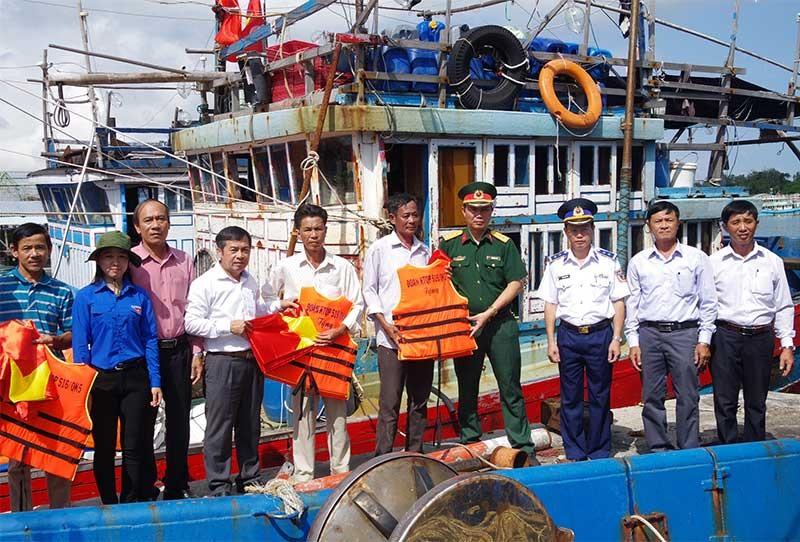 Chỉ huy Đoàn Tam Quang tặng ngư yếu cụ, cờ Tổ quốc cho ngư dân xã ven biển Tam Quang. Ảnh: V.HÙNG