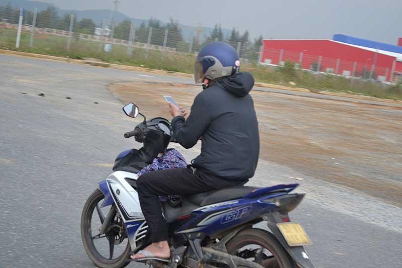 Đang đi xe máy mà sử dụng điện thoại di động sẽ bị xử phạt 100 - 200 nghìn đồng. Ảnh: T.C.T