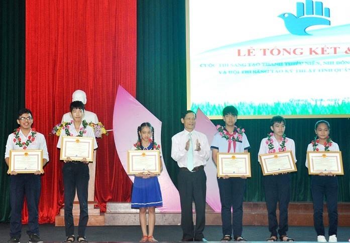Trần Nguyễn Thanh Thanh (thứ 3 từ trái sang) nhận giải nhất Cuộc thi sáng tạo thanh thiếu niên nhi đồng tỉnh lần thứ 12 - năm 2019 với sản phẩm túi xách làm từ xơ mướp. Ảnh: L.C