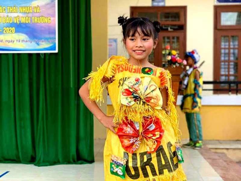 Một học sinh trình diễn thời trang bằng đồ tái chế, gửi thông điệp bảo vệ môi trường. Ảnh: A.L.T