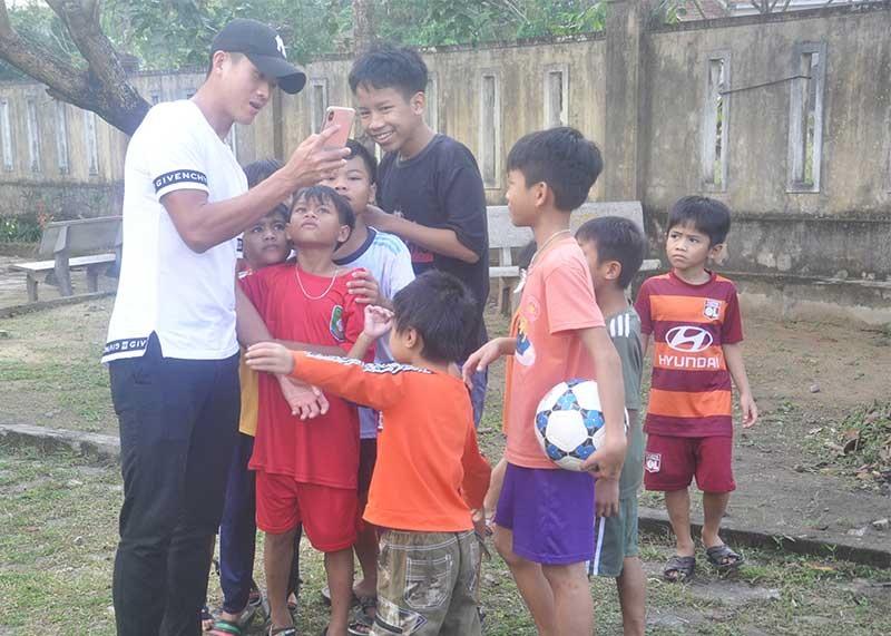 Cầu thủ Hà Minh Tuấn chia sẻ hình ảnh chụp cùng trẻ em Làng Hòa Bình. Ảnh: T.V