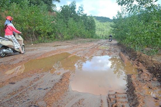 Nhân viên nhà máy phải vất vả băng qua con dốc trơn trợt, lầy lội. Ảnh: C.T