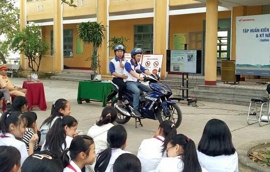 Hướng dẫn học sinh cách thức ngồi sau xe máy. Ảnh: C.T