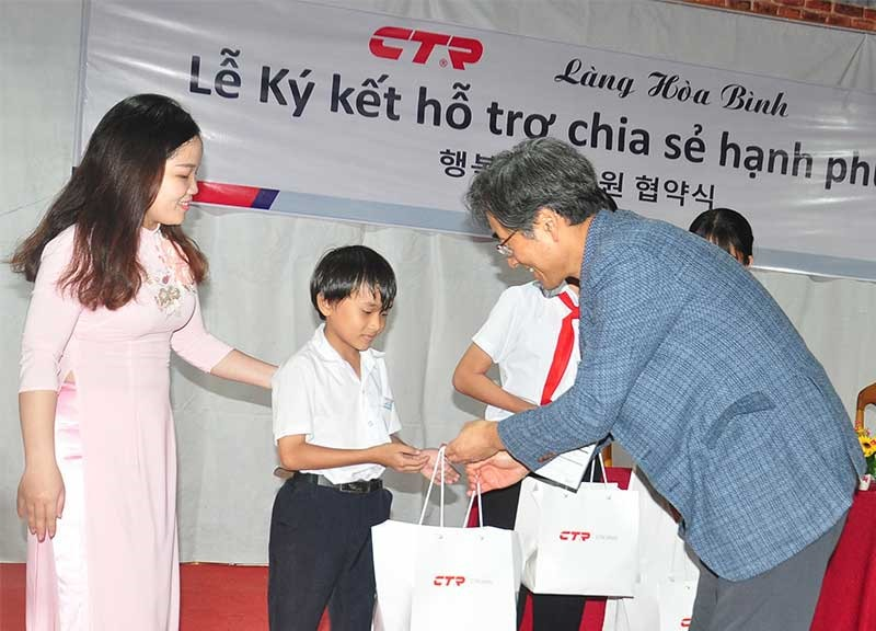 Leader of CTR Vina comapny (Right) gives gifts to students in Hoa Binh Village