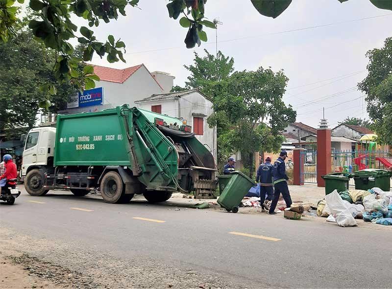 Công nhân Công ty CP Môi trường đô thị Quảng Nam thu gom rác tồn đọng tại xã Tam Dân, huyện Phú Ninh. Ảnh: THANH THẮNG