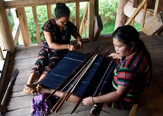Pơling Muối đang truyền dạy kỹ thuật dệt cho một thợ trẻ. Ảnh: TẤN VỊNH