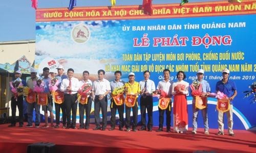Phó Tổng cục trưởng Tổng cục TD-TT Lê Thị Hoàng Yến và lãnh đạo tỉnh tặng cờ và hoa cho các đoàn tham gia giải bơi. Ảnh: T.V