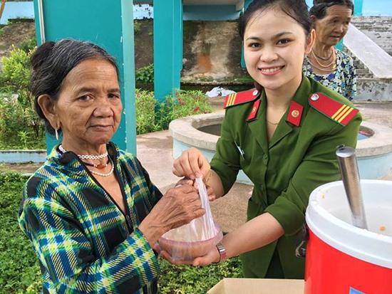 Chiến sĩ Công an huyện Đông Giang trao suất cháo từ thiện cho người bệnh. Ảnh: Đ.N