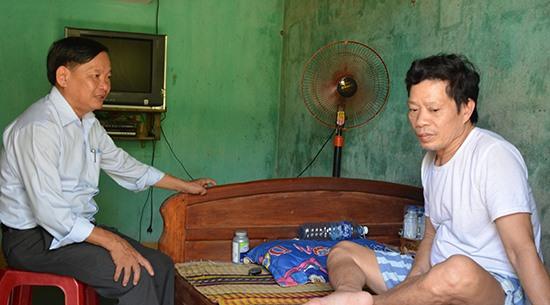 Ông Dương Văn Hùng - Giám đốc BHXH huyện Tiên Phước đến thăm hỏi ông Vũ Quang Tiến (thôn 1, Tiên Cảnh) bị tai biến mạch máu não. Ảnh: N.H