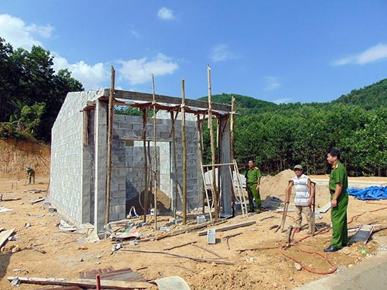 Anh Hồ Văn Thắng cùng cán bộ Công an huyện Phước Sơn bên căn nhà tình nghĩa đang được xây dựng. Ảnh: T.N