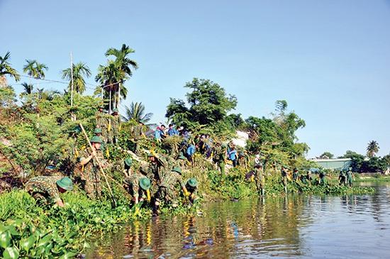 Lực lượng thanh niên tình nguyện tham gia vớt bèo tây, dọn vệ sinh các hồ điều hòa Tam Kỳ. Ảnh: VINH ANH