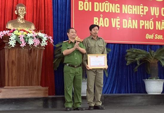 Đại tá Phan Văn Dũng - Phó Giám đốc Công an tỉnh trao giấy khen cho ông Trần Văn Chiến. Ảnh: V.K