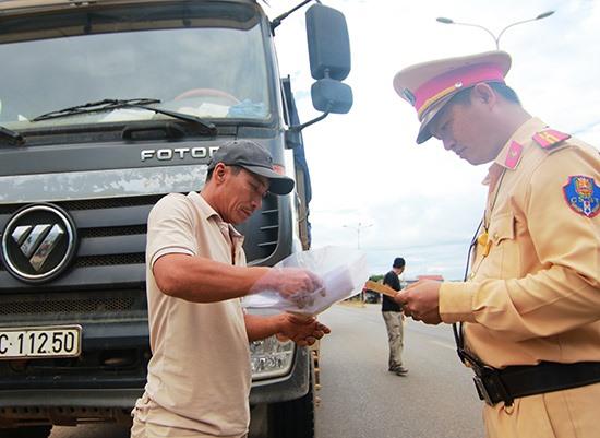 Song song với việc xử lý vi phạm, CSGT kết hợp tuyên truyền, nhắc nhở lái xe chấp hành các quy định trong quá trình vận tải vật liệu xây dựng. Ảnh: T.C