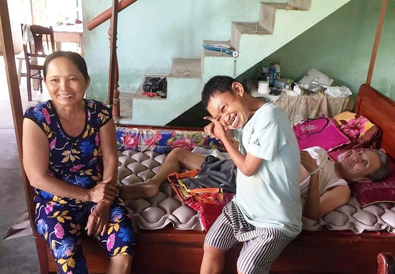 Bà Chung bên người chồng bị thương tật, mù mắt, lại bị tai biến nằm một chỗ và đứa con bị nhiễm chất độc da cam nặng mất khả năng điều khiển hành vi. Ảnh: MỸ LIÊN