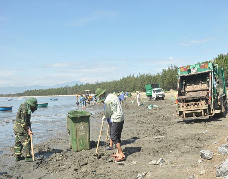 Các lực lượng phối hợp thu gom rác thải tại bãi biển Thuận An, xã Tam Hải sáng 8.8. Ảnh: NG.ĐOAN