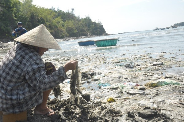 Người dân phải giũ bùn cát để thu gom rác thải nhựa. Ảnh: N.Đ
