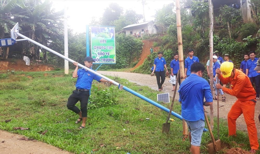 Đoàn viên thanh niên bắt điện chiếu sáng tại thôn 1, xã Trà Tập. Ảnh: THÁI CƯỜNG