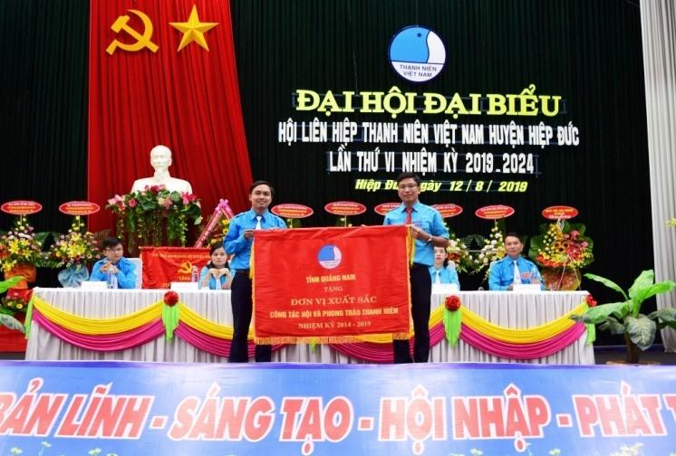 Tặng Cờ thi đua xuất sắc trong công tác hội và phong trào thanh niên cho Hội LHTN Việt Nam huyện Hiệp Đức. Ảnh: THÁI CƯỜNG