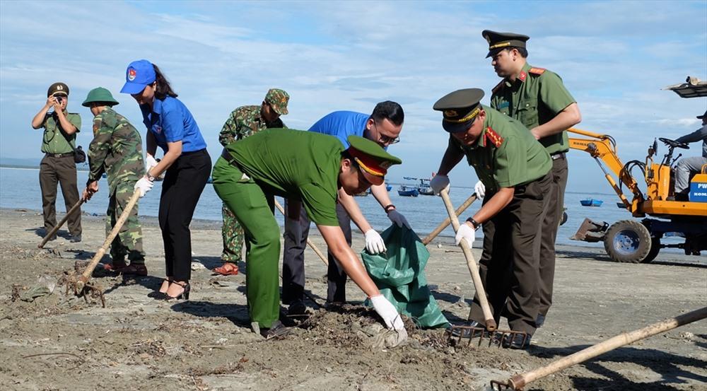 Lực lượng công an, bộ đội, ĐVTN địa phương tham gia dọn rác tại bãi biển. Ảnh: M.L