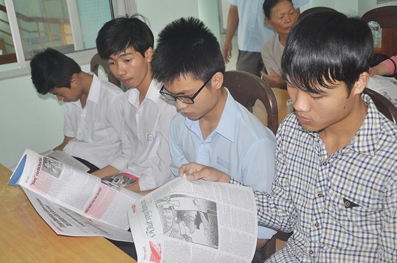 Trong khi chờ buổi lễ bắt đầu, các em học sinh nhận giải tranh thủ đọc Báo Quảng Nam. Ảnh: X.P