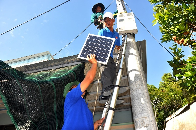 Lực lượng thanh niên tình nguyện hỗ trợ đơn vị thi công lắp đặt đèn năng lượng mặt trời cho nhân dân Cù Lao Chàm. Ảnh: V.ANH