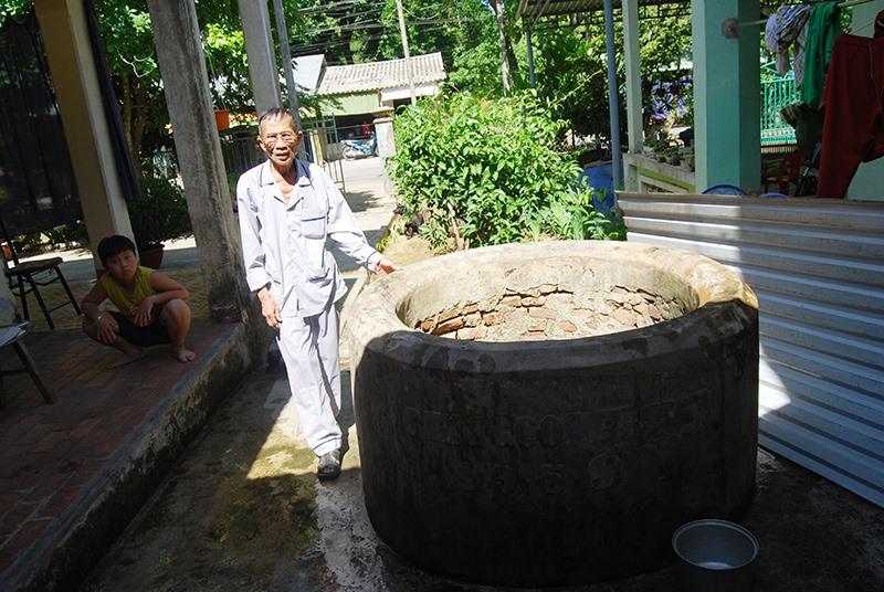Ông Nguyễn Văn Mích bên giếng Chăm ở sân nhà tại làng Khương Mỹ (xã Tam Xuân 1). Ảnh: HOÀNG MINH