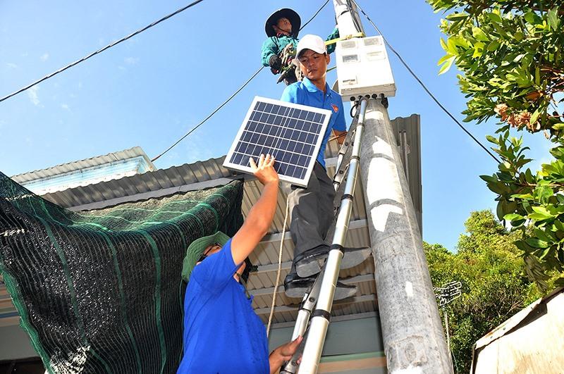 Thanh niên tình nguyện hỗ trợ lắp đặt công trình thắp sáng đường quê bằng đèn năng lượng mặt trời trên xã đảo Tân Hiệp. Ảnh: V.ANH