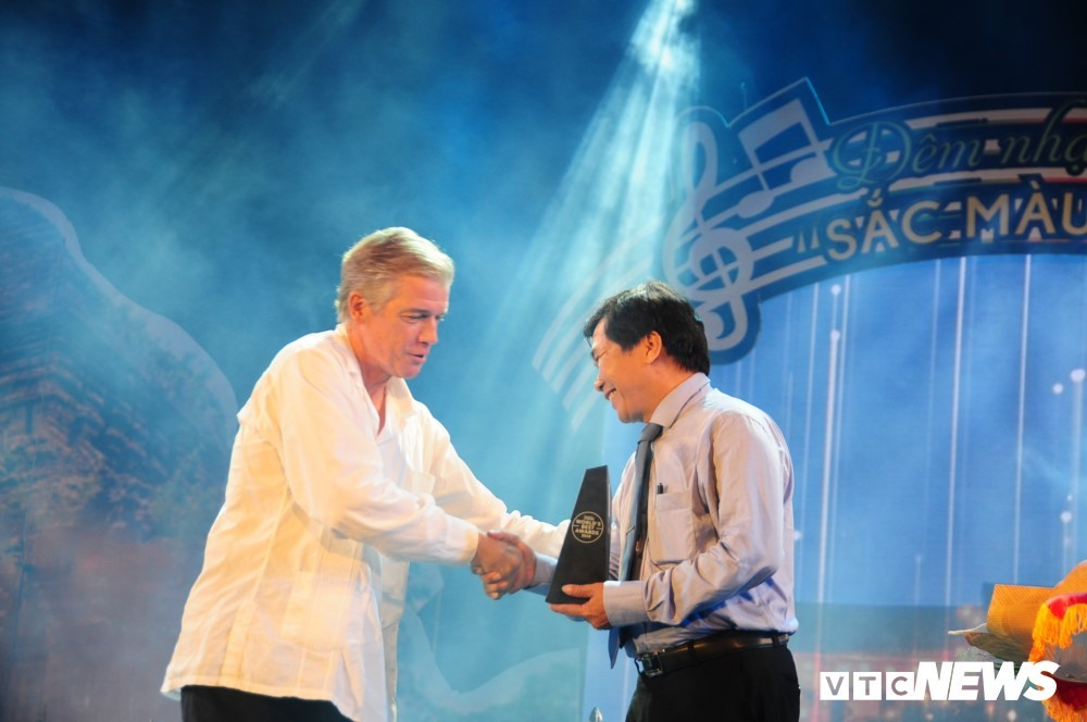 Represetative of the Travel & Leisure (L) gives the award to Hoi An city's leader.