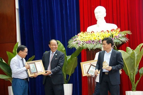 Quang Nam leaders (right) give souvenirs to contributors to the local development