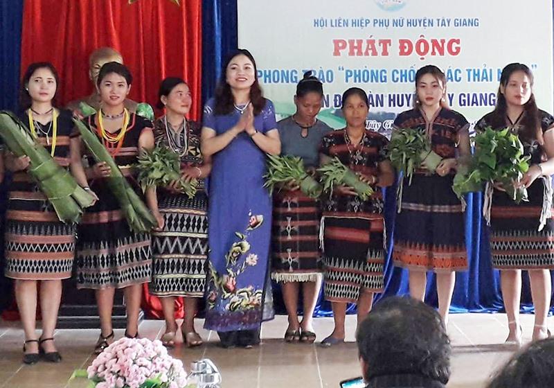 Hội LHPN huyện Tây Giang tuyên truyền cho hội viên sử dụng gói thực phẩm bằng lá chuối, lá dong thay thế túi nylon. Ảnh: HIỀN THÚY