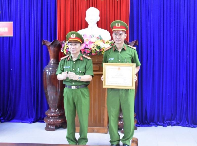 Đại tá Nguyễn Đức Dũng - Phó Giám đốc Công an tỉnh trao Bằng khen của Chủ tịch UBND tỉnh cho Phòng Cảnh sát hình sự. Ảnh: C.V