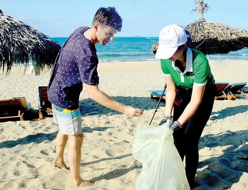 Local people and tourists collect waste at beach in Hoi An city, Quang Nam province