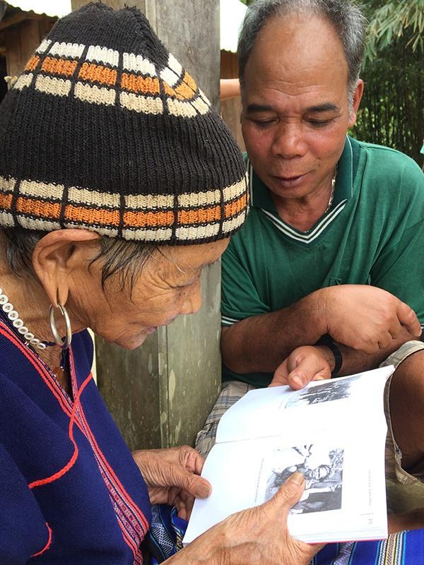"""Cụ bà Bhơnướch Thị Bhươi (95 tuổi, con dâu tộc họ Bhơriu) xúc động kể cho con cháu chuyện của tộc họ Bhơriu qua hình ảnh từ cuốn sách """"Những kẻ săn máu"""" của Le Pichon. Ảnh: BHƠRIU QUÂN"""