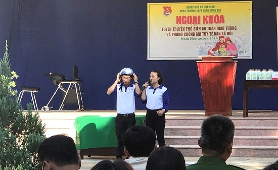 Hướng dẫn viên của Tiến Thu - Tiến Đức hướng dẫn học sinh cách đội mũ bảo hiểm cách quy cách. Ảnh: CT
