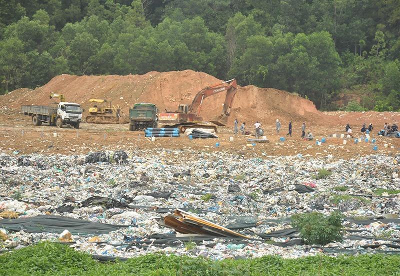Đến trưa ngày 25.9, công nhân Công ty CP Môi trường đô thị Quảng Nam bắt đầu tiến hành xử lý chế phẩm và phủ bạt che đậy rác tại hố số 1 của khu chứa và xử lý rác thải xã Tam Xuân 2. Ảnh: Đ.C