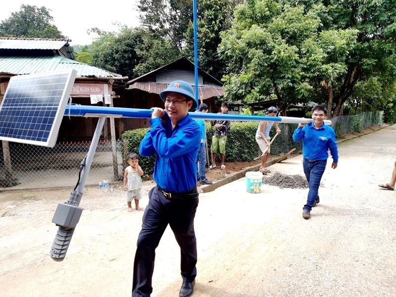 Lực lượng thanh niên tiến hành thi công lắp đặt các trụ điện chiếu sáng bằng năng lượng mặt trời. Ảnh: CTV