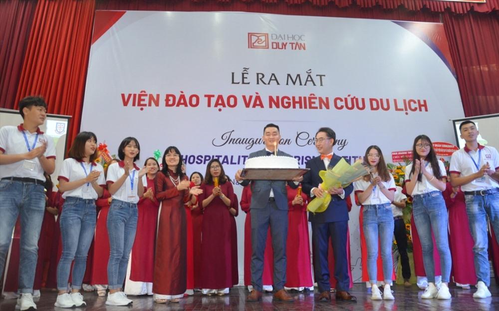 GS-TS. Lim Sang Teak - Viện trưởng Viện Đào tạo và nghiên cứu du lịch - Đại học Duy Tân (người cầm hoa) chụp ảnh lưu niệm cùng cán bộ, sinh viên khoa du lịch nhà trường. Ảnh: N.T.B